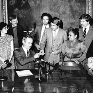 Gov. Anthony Earl signs the Consenting Adults Bill in 1983 decriminalizing homosexual acts and other private sex acts. Such a bill was first proposed by Lloyd Barbee in the early 1970s.  Looking on are (left to right) Dan Curd, Linda Kessel, Dick Wagner, State Representative John Manske, State Representative David Clarenbach (author), State Representative Marcia Coggs (Barbee's successor, State Representative David Travis, and an unidentified woman.